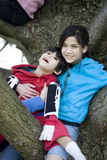 Sister holding disabled brother in tree Stock Photo