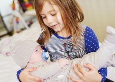 Sister holding newborn brother stock photography