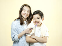 Sister holds toothbrush for brother. Royalty Free Stock Image