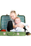Sister hugging brother, sitting in suitcase stock photo