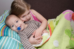 Sister hugging her brother in bed Stock Images