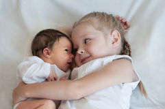 Sister hugs her younger brother. 5 years old sister hugs her younger 2 weeks old brother Stock Photo