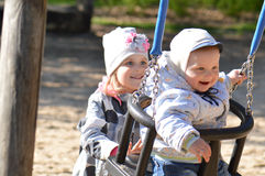 Sister with infant brother. Girl play with infant brother boy on swing Stock Image