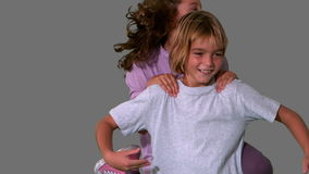 Sister jumping on brothers back on grey background Royalty Free Stock Image