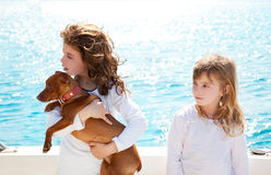 Sister kid girls with dog on the sea Stock Image