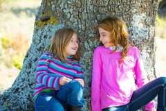 Sister kid girls smiling sit relaxed in a oak tree trunk Royalty Free Stock Photo