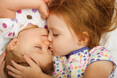 Sister kissing baby. Older sister kissing baby in bed Stock Images