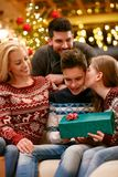 Sister kissing brother for Christmas. Sister kissing brother and give him gift for Christmas Royalty Free Stock Photo