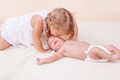 Sister kissing her baby brother. Loving sister kissing her small baby brother Royalty Free Stock Photo