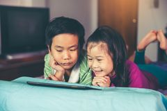 Sister kissing her brother on the cheek while they using tablet. Asian children using digital tablet on bed. Sister smiling but her brother look displeased Stock Image