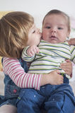 Sister kissing her brother. Little girl kissing her brother Royalty Free Stock Photography