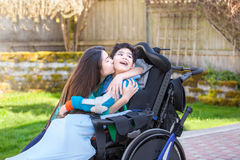 Sister kissing and hugging disabled little brother in wheelchair. Sister kissing and hugging disabled little nine year old  brother in wheelchair outdoors Royalty Free Stock Image