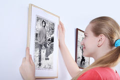 Sister looks photo brother on white wall Stock Photos