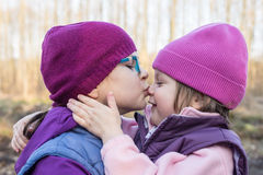 Sister lovingly kissing her younger sister Royalty Free Stock Photos