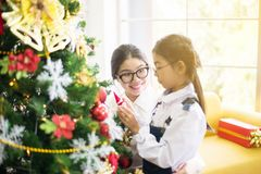 Sister make a christmas gift box to younger sister for xmas holiday,Happy and smiling together. At home stock photo