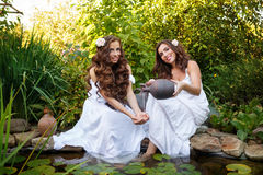 Sister pour water from a jug in her arms girl. Two sisters in white dresses at the pond with water lilies. Girl pours water from earthenware jug on the old Stock Photo