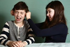 Sister pull brother ear as a loss in argument. Wage close up photo royalty free stock photo