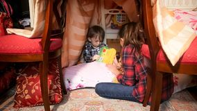 Elder sister reading book with toddler boy in tent at bedroom. Sister reading book with toddler boy in tent at bedroom Royalty Free Stock Photography