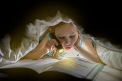Sister are reading a book under a blanket with flashlight. Pretty young girl having fun in children room. Royalty Free Stock Photo