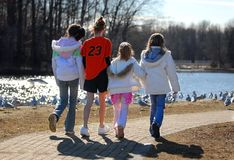 Sister's Hand in Hand. Four sister's walking hand in hand at the neighborhood park on a blustery February afternoon Royalty Free Stock Photography