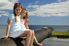 Sister's summer vacation portrait. Sister's sitting on a historical cannon Royalty Free Stock Image