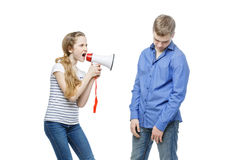 Sister screaming at brother. Teen age girl screaming at boy through megaphone. Brother and sister isolated on white background. Copy space Royalty Free Stock Photo