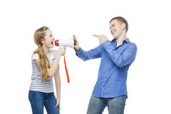 Sister screaming at brother. Teen age girl screaming at boy through megaphone. Brother and sister isolated on white background. Copy space Royalty Free Stock Photos