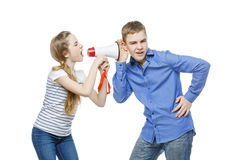 Sister screaming at brother. Teen age girl screaming at boy through megaphone. Brother and sister isolated on white background. Copy space Royalty Free Stock Photography