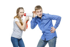 Sister screaming at brother. Teen age girl screaming at boy through megaphone. Brother and sister isolated on white background. Copy space Stock Image