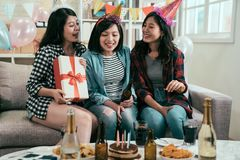 Sister sending gift box for surprised. Group of young friends with cake and bottles of drink celebrating birthday in home interior. sister sending gift box for stock photography
