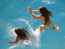 Sister Splash. Two sisters jump into the water in tandem Royalty Free Stock Photos