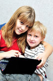 Sister teaching brother using notebook. Teenage sister teaching brother using notebook Royalty Free Stock Images