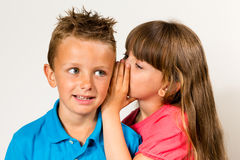 Sister telling secret to brother Stock Image