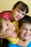Sister and two brothers. A sister and two brothers are hugging. All 3 are smiling and happy royalty free stock image