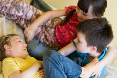 Sister and two brothers. A sister and two brothers are hugging and playing while they are sitting stock images