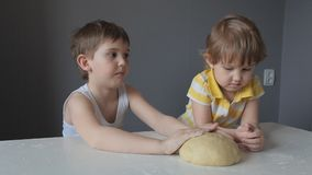 The sister was offended at her brother that he did not give her to stroke the dough with her hands stock video