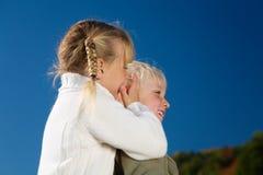 Sister Whisper. Girl whispering a secret in her sister's ear stock photo