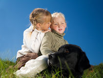 Sister, Whisper, Dog. Girl whispering a secret in her sister's ear, both sitting upon their (very patient) dog royalty free stock photo