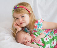 Sisters. Sister Laying with New Baby Sister Stock Photo