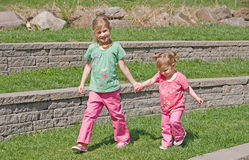 Sisters. Holding Hands Walking in the Park Stock Images