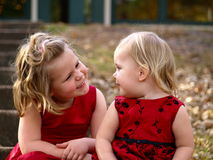 Sisters. Two adorable sisters smiling at each other Royalty Free Stock Image