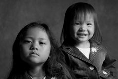 Sisters. Two asian sisters, one with a smile and the other sad Royalty Free Stock Photography
