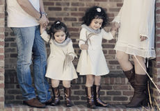 Sisters amazed. Two adorable sisters are holding their parents hands Royalty Free Stock Image