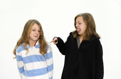 Sisters arguing. Two sisters young girls arguing together and pointing finger Royalty Free Stock Photo