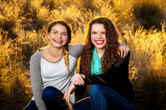 Sisters In A Backlit Field. Two smiling sisters sit together in the late afternoon sunlight.  They are backlit, as is the field that they are in Royalty Free Stock Images