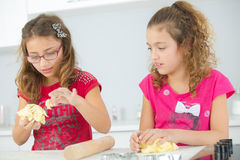 Sisters baking in kitchen Stock Image