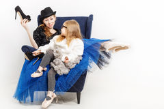 Sisters ballerina and high-heeled shoes. The elder sister and little girl ballerina are sitting in a chair. They keep their shoes on high heels. Girls in ballet Stock Image