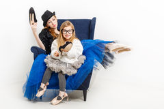 Sisters ballerina and high-heeled shoes. The elder sister and little girl ballerina are sitting in a chair. They keep their shoes on high heels. Girls in ballet Stock Photo
