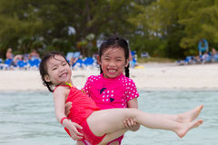 Sisters at the Beach. Big sister carrying young sister at the beach royalty free stock image