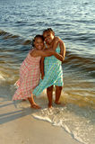 Sisters at the beach. Two smiling hugging african american sisters on a beach Stock Image